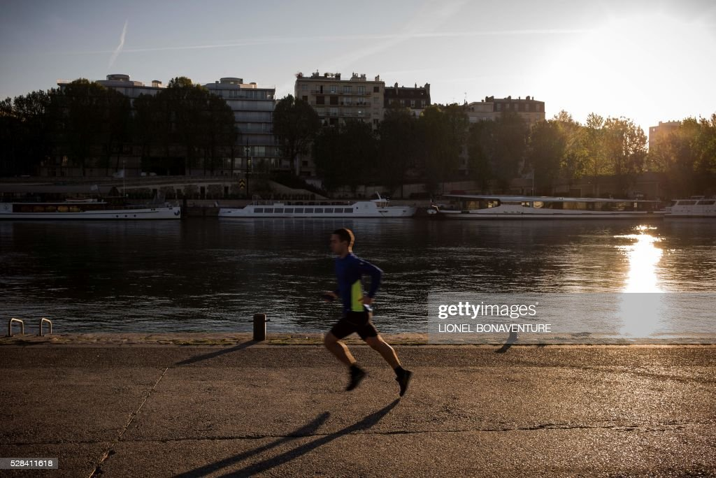 A man jogs on the banks of the Seine river, on May 5, 2016 in Paris. / AFP / LIONEL