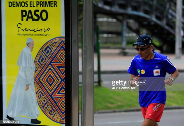 A man jogs past a sign reading 'Let's all take the first step' ahead of Pope Francis' upcoming visit in Bogota on August 23 2017 Pope Francis will...