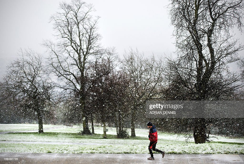 A man jogs under falling snow at Alexandra Palace in London on January 14, 2013. Snow hit parts of England with up to 10cm expected to fall in some areas, prompting fears of travel chaos. AFP PHOTO/ADRIAN DENNIS