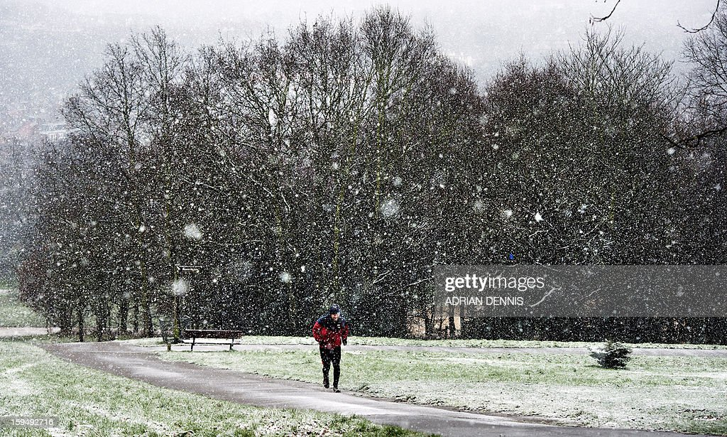 A man jogs up the hill through snow at Alexandra Palace in London on January 14, 2013. Snow hit parts of England with up to 10cm expected to fall in some areas, prompting fears of travel chaos.