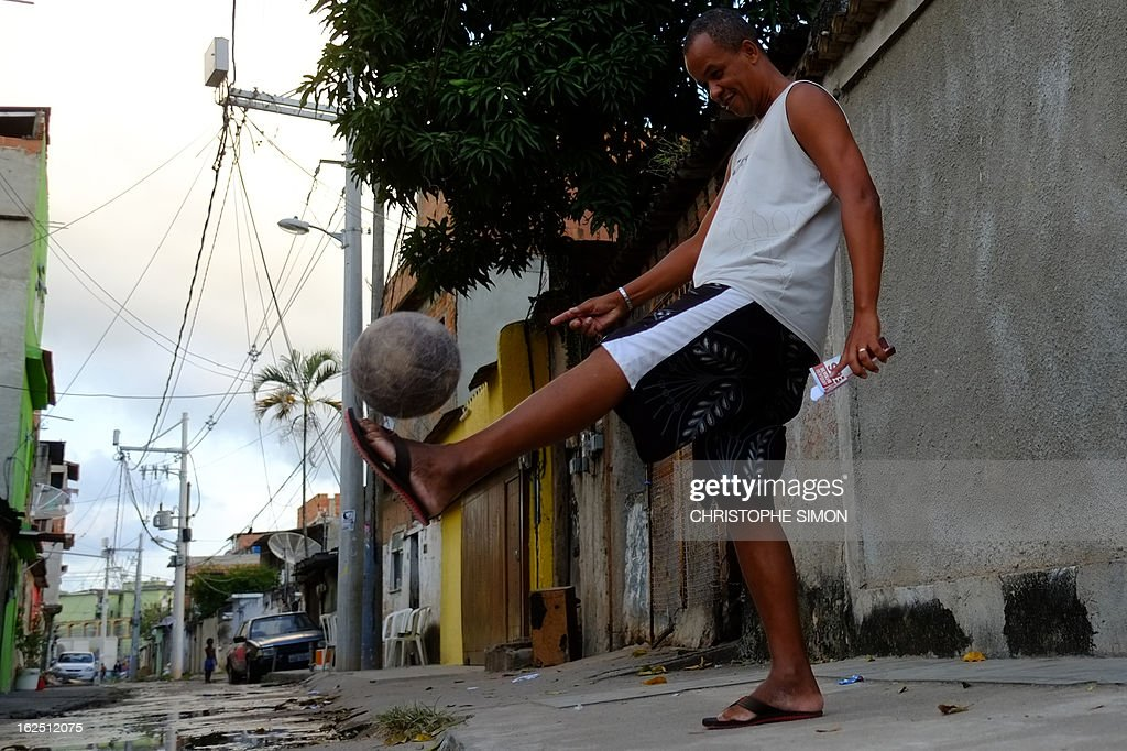 A man juggles with a ball as he holds a religious book at Rio de Janeiro's Cidade de Deus shantytown, in Brazil, on February 23, 2013. AFP PHOTO/Christophe Simon