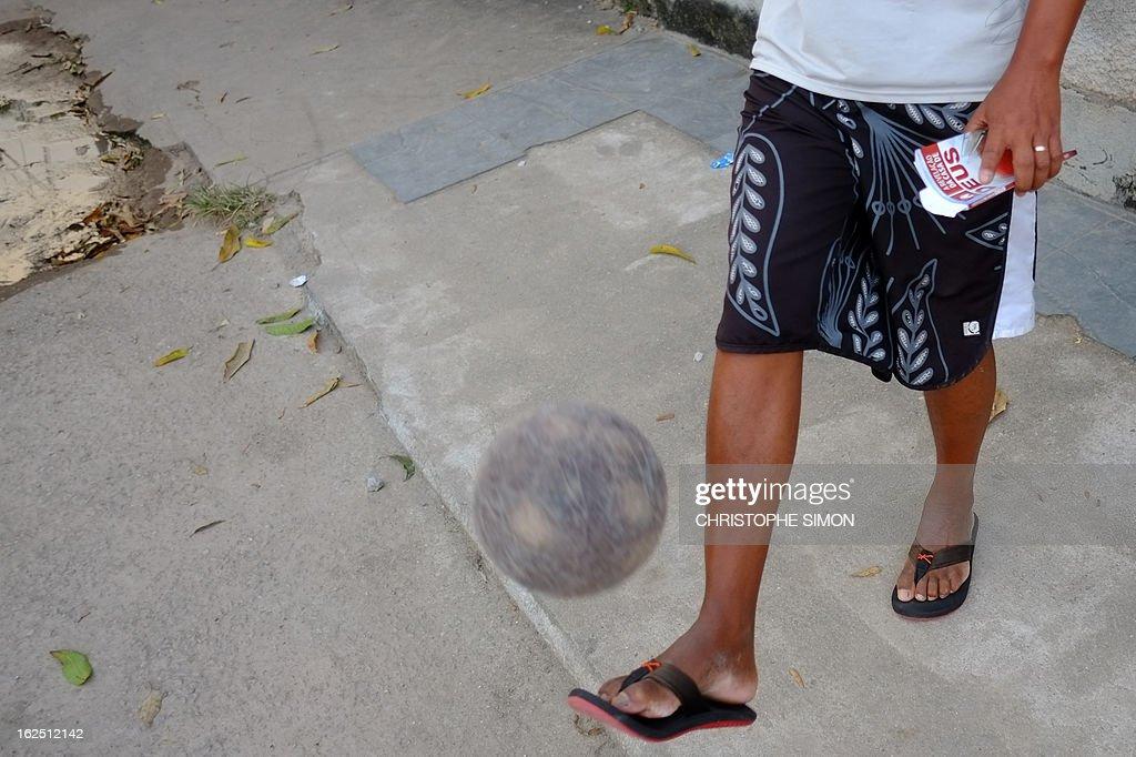 A man juggles with a ball as he holds a religious book at Rio de Janeiro's Cidade de Deus shantytown, in Brazil, on February 23, 2013. AFP PHOTO/Christophe Simon