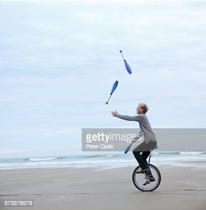 Man juggling pins on unicycle on beach : Stock Photo