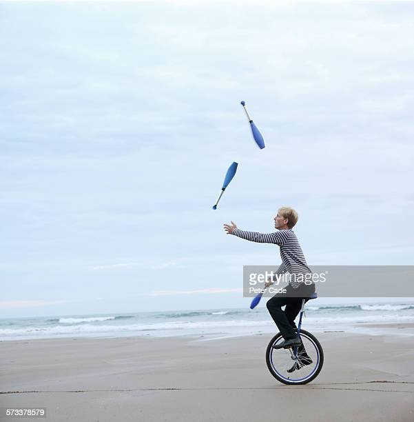 Man juggling pins on unicycle on beach