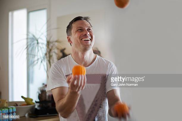 man juggling with oranges, smiling