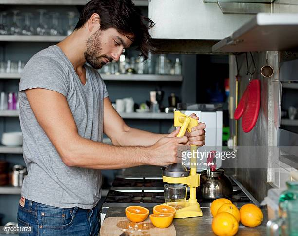 man juicing oranges