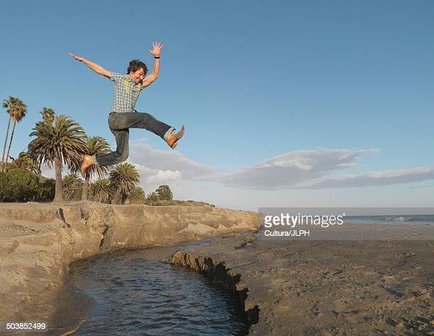 Man jumping across brook