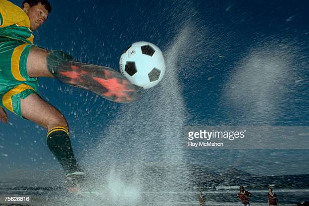 Man jumping and kicking football on beach, low angle view