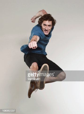 Man jumping and punching in air, smiling, portrait