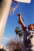 Man jumping and reaching for a basketball