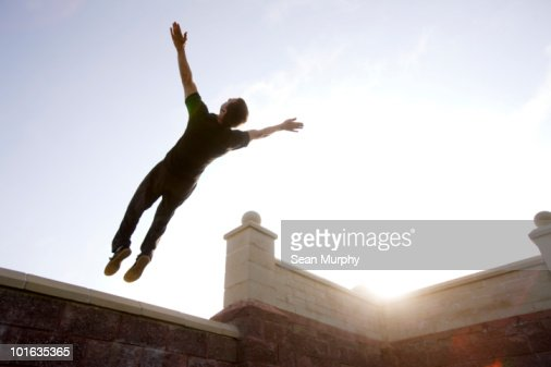Man jumping backwards off ledge