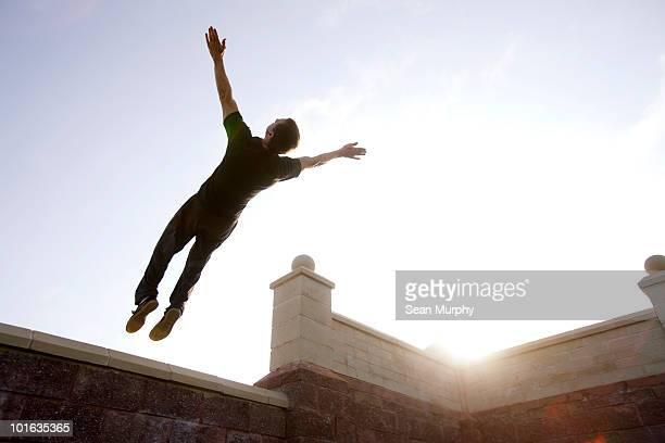 Man jumping backwards off ledge