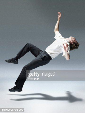 Man jumping backwards, side view