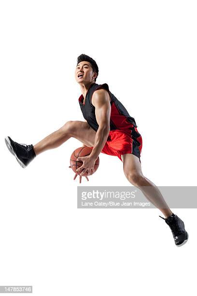 Man jumping doing basketball tricks