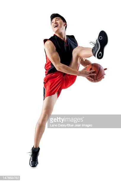Man jumping doing basketball tricks