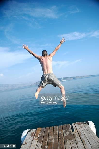 Homme sautant du quai dans l'eau de mer bleue