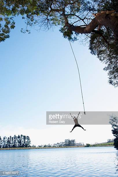 Man jumping from rope swing into lake