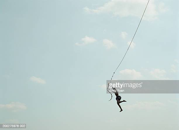 Man jumping from rope, view from below