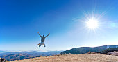 Man jumping high in the sky on a mountain view