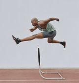 Man jumping hurdle, side view