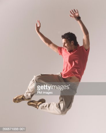 Man jumping in air, smiling : Stock Photo