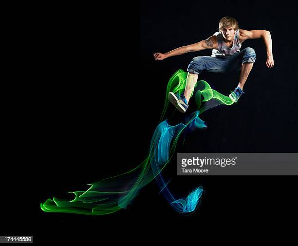 man jumping in air with light trails