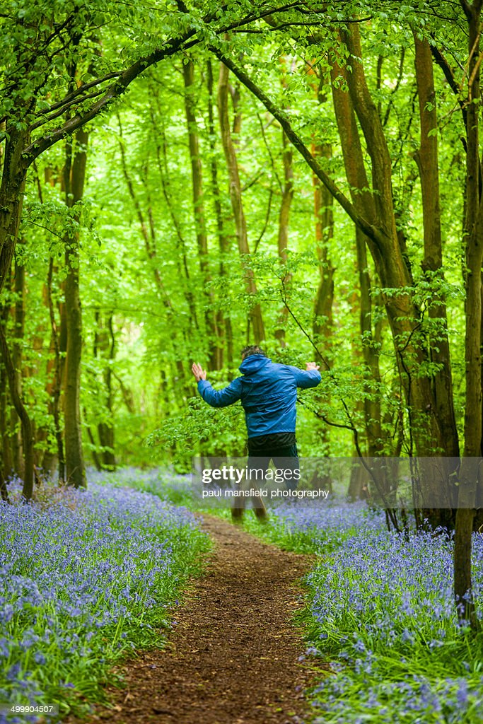 Man jumping in bluebell wood