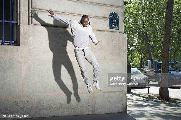 Man jumping in front of wall