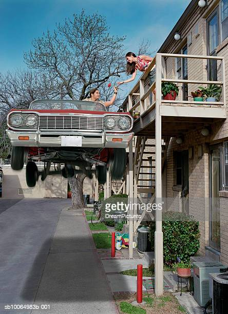 Man jumping in lowrider to reach woman on balcony (Digital Composite)