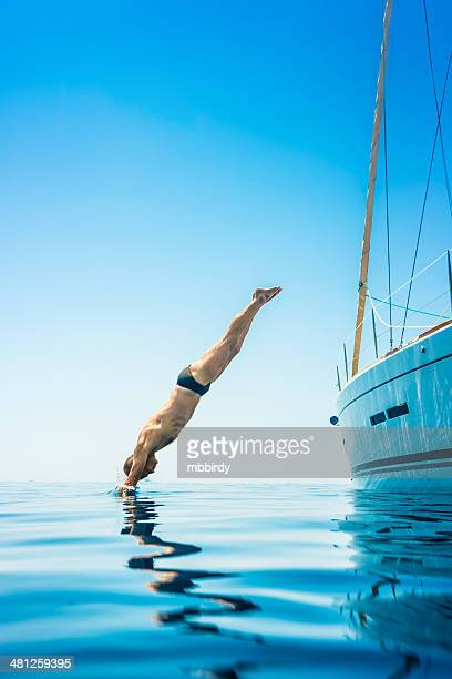 Man jumping in sea from sailboat