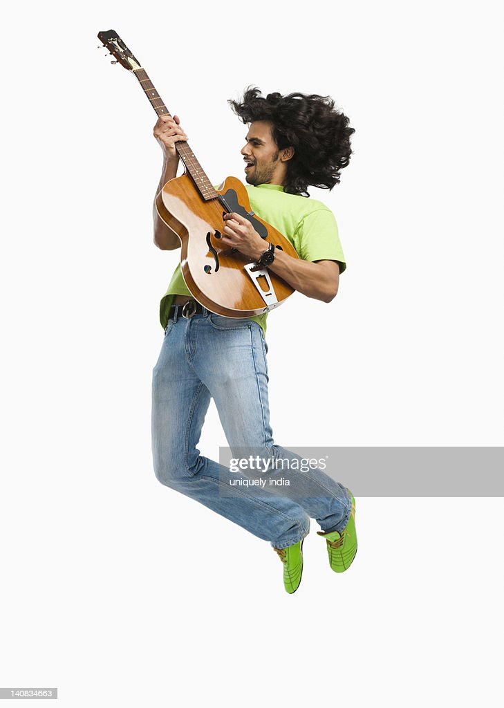 Man jumping in the air while playing a guitar : Stock Photo
