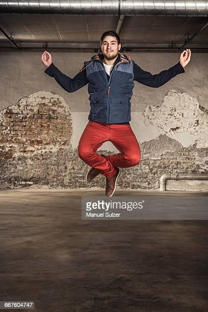 Man jumping inside old warehouse