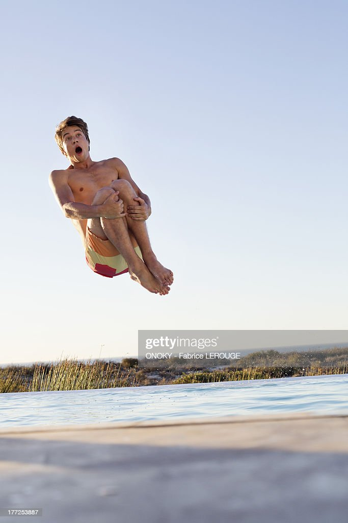 Man jumping into a swimming pool : Stock Photo