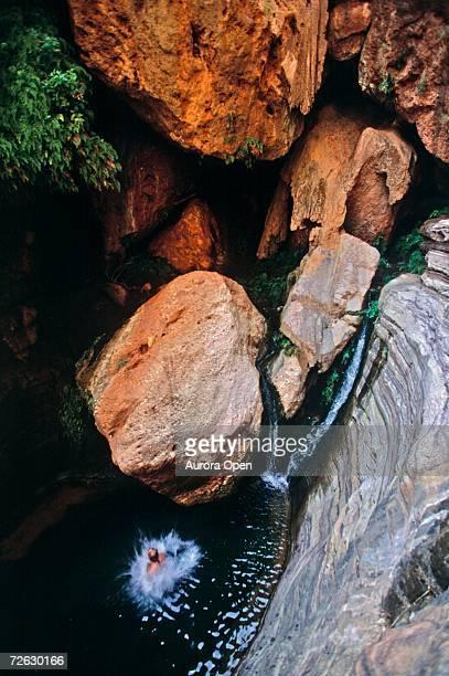 A man jumping into pool in desert canyon, Grand Canyon, Arizona.