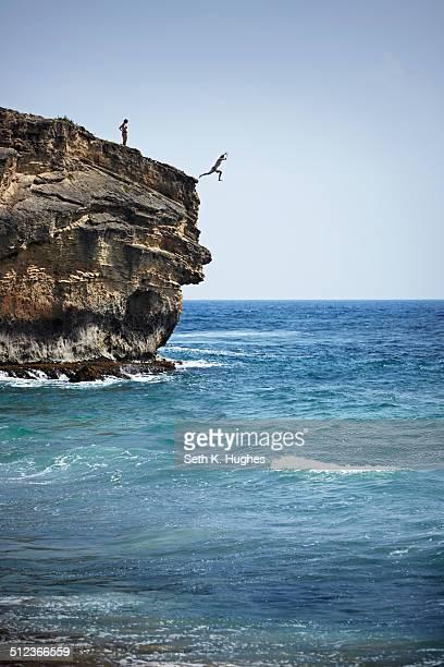 Man jumping into sea from cliff, Poipu, Kaua'i, Hawaii, USA