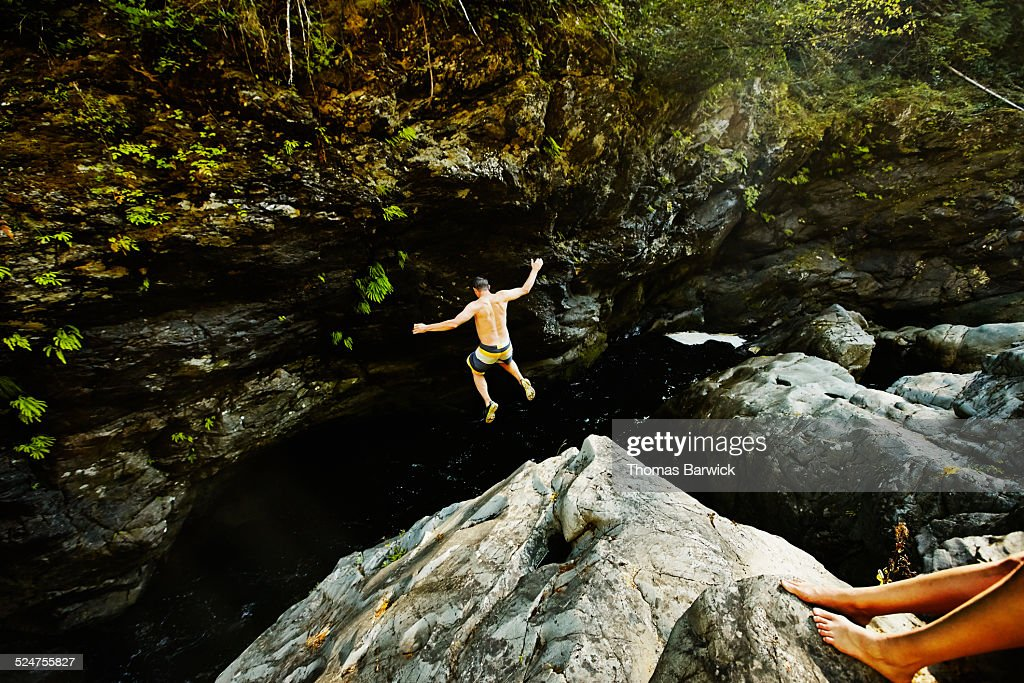 Man jumping into swimming hole arms outstretched : Stock Photo