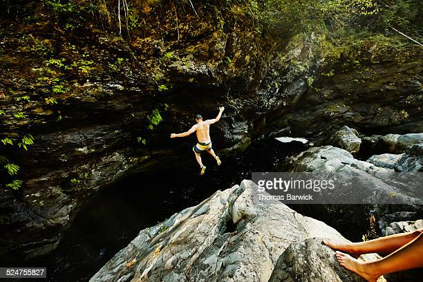 Man jumping into swimming hole arms outstretched