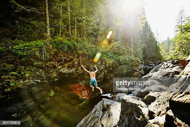 Man jumping into swimming hole on summer afternoon
