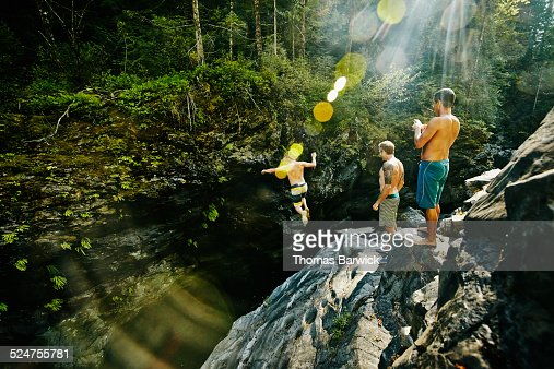 Man jumping into swimming hole while friends watch