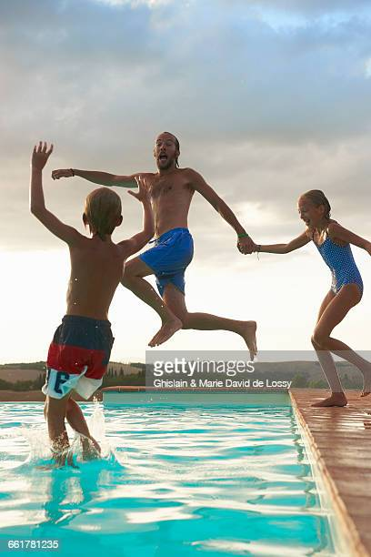 Man jumping into swimming pool with daughter and son, Buonconvento, Tuscany, Italy