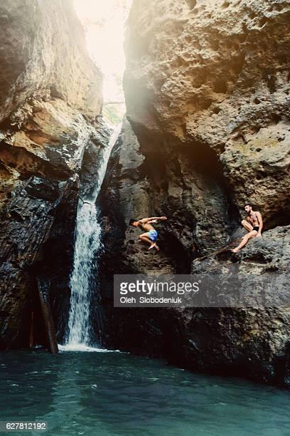 Man jumping into tropical waterfall