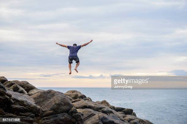 Man jumping mid air with rocks and sea