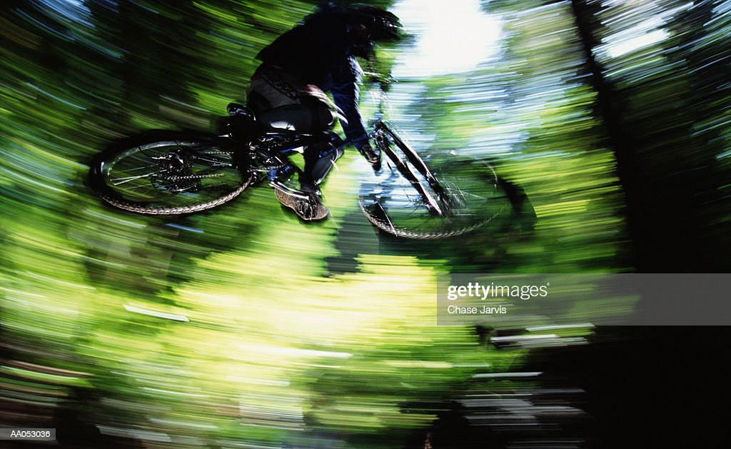 Man jumping mountain bike on trail, low angle view (blurred motion) : Stock Photo