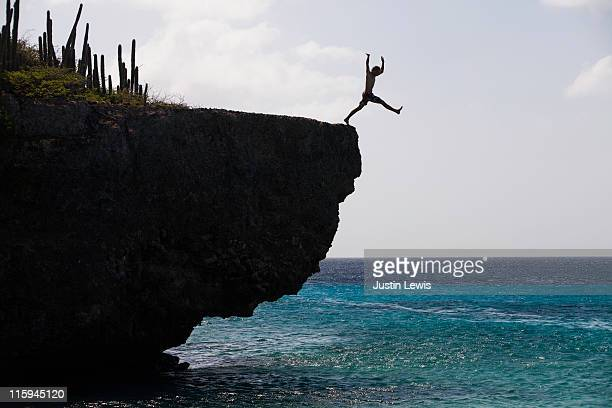 Man jumping off a cliff into the ocean.