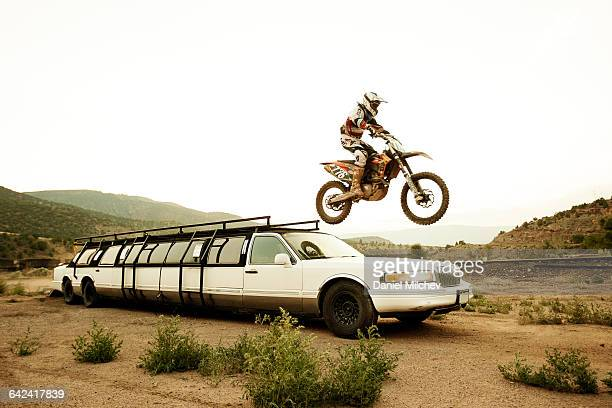 Man jumping off limousine with dirt bike.