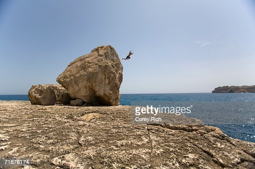 A man jumping off of a boulder into the sea. : Stock Photo