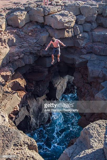 Man Jumping Off of Cliff into Ocean Opening Surrounded by Rocks at South Point on the Big Island Of Hawaii
