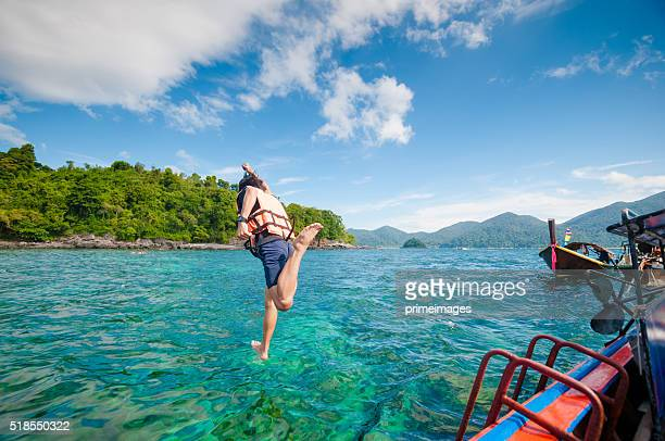 Man jumping off the boat into the ocean