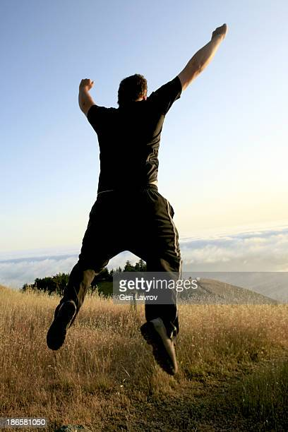 Man jumping on a mountaintop above the clouds