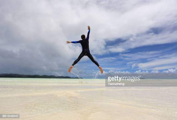 A Man Jumping on a Tropical White Sand Beach of Palau